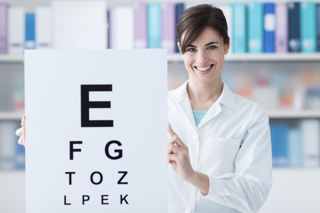 Female professional oculist holding an eye chart and smiling at camera, medical examination and eye care concept